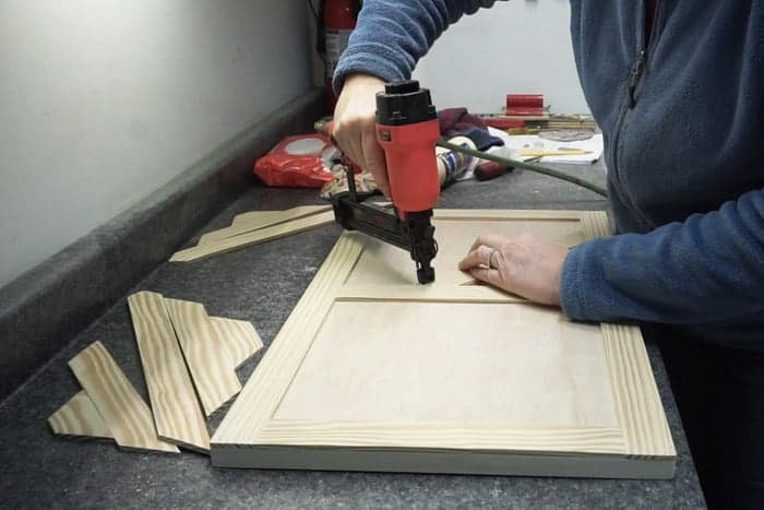 Brad nailer attaching trim to front of cabinet door.