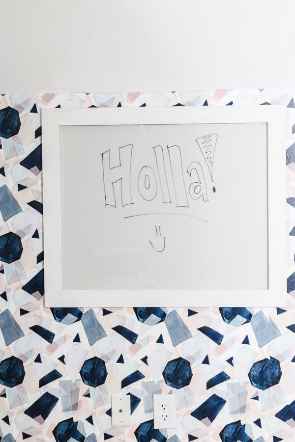Glass white board with white frame hung on colorful graphic wallpaper.