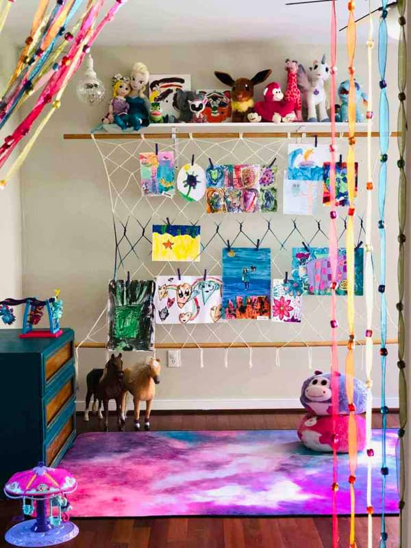 Colorful artwork display in colorful bedroom hung with child's art.