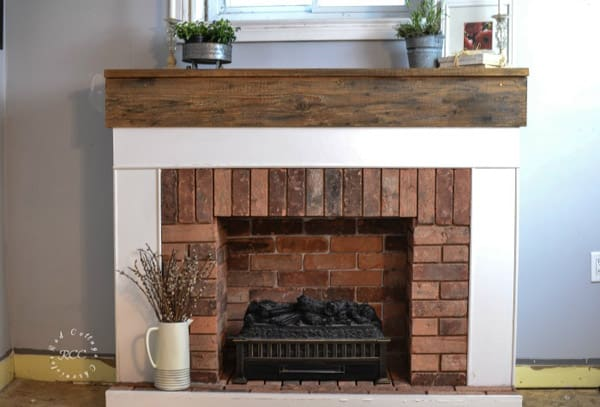 Brick fireplace with white trim and wood mantel.