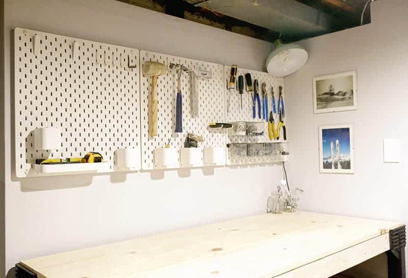 Pegboard wall system hung in basement workshop.