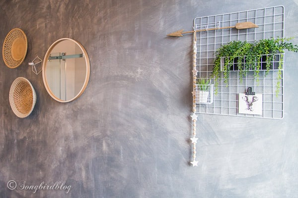 Faux painted concrete wall hung with baskets.