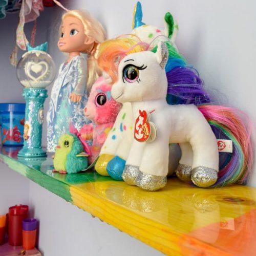 Rainbow painted shelves in little girl's room.