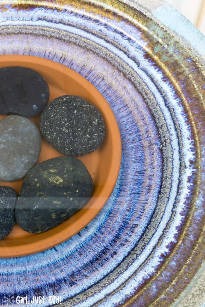 Birdbath filled with water and blue mexican rocks.