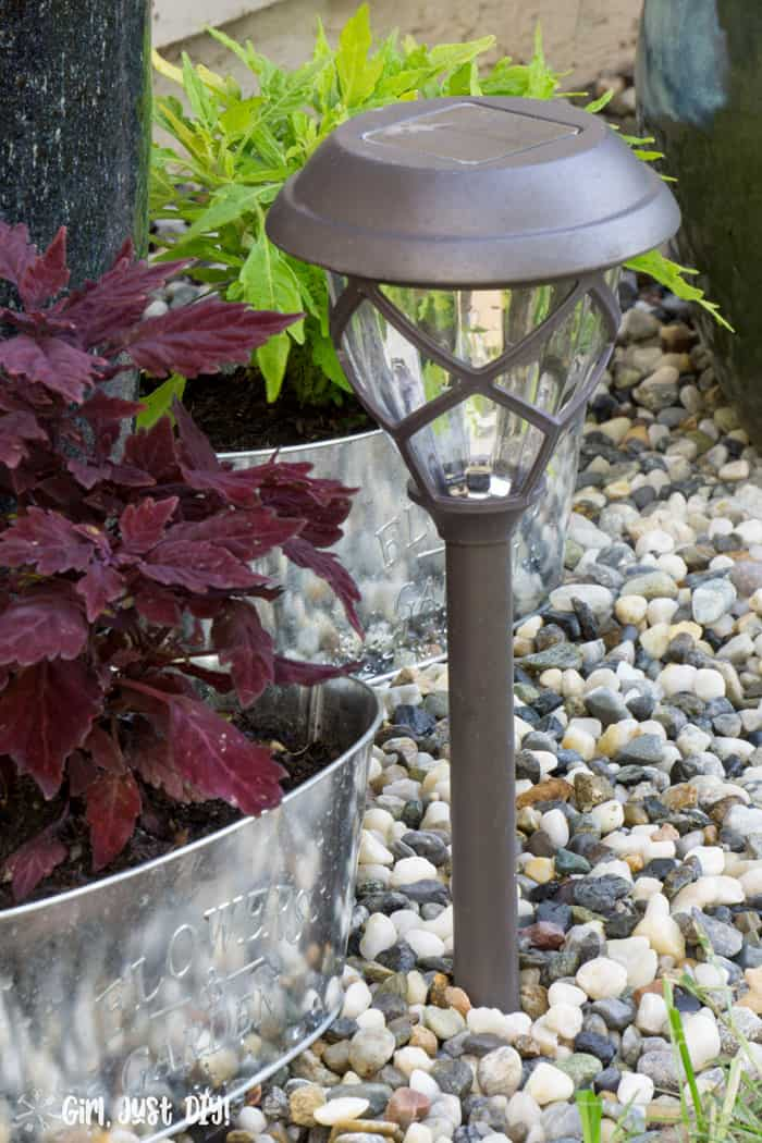 Solar path light next to coleus plant in rock flower bed.