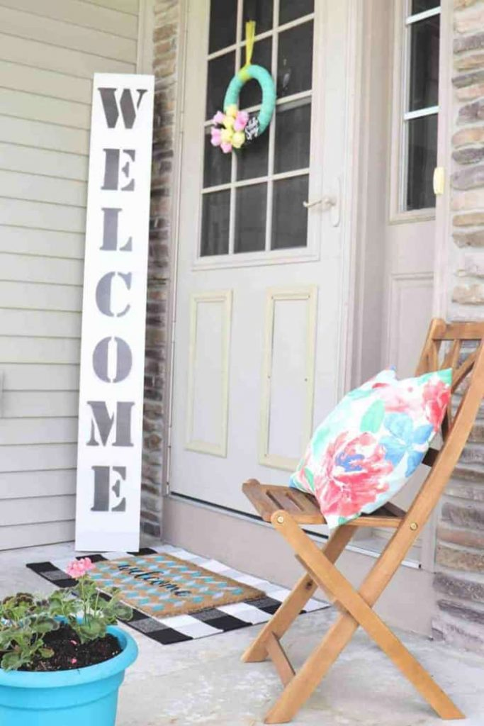 Outdoor DIY projects showing welcome sign and colorful pillow on folding wood porch chair.
