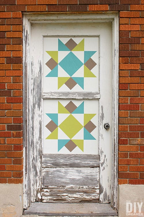 Barn Quilt painted squares in windows of old wood door.
