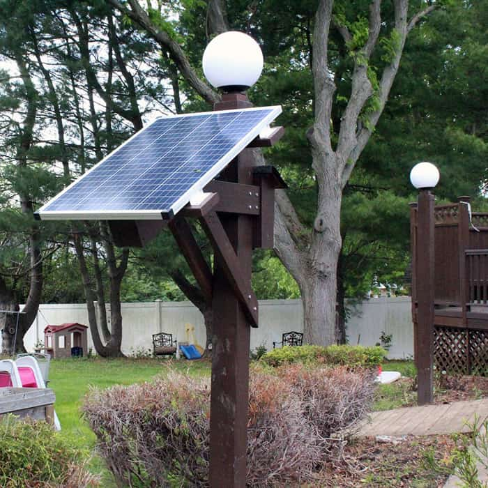 Light Poles with solar panel on side in backyard.