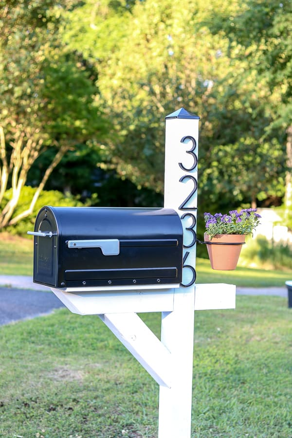 Black Mailbox on white post with address and hanging flower pot.