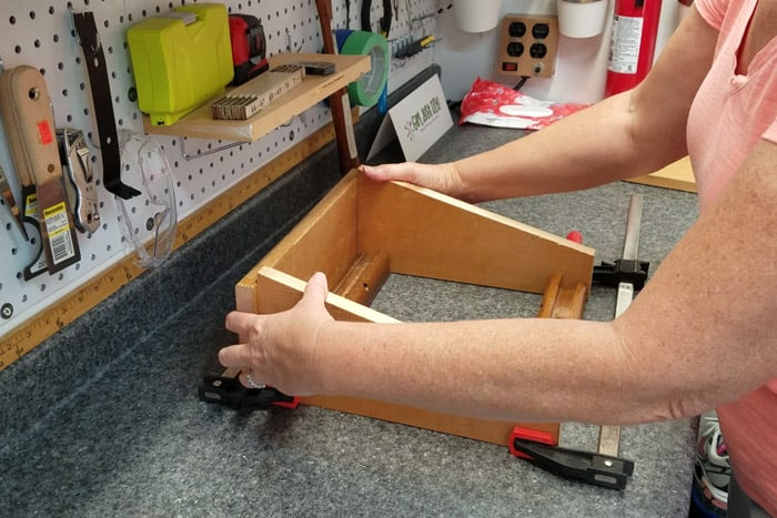 Clamps holding legs evenly spaced apart lwith hands holding a board at back to get them square.