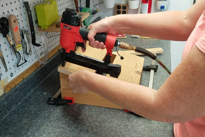 Attaching final top board to footrest legs with brad nailer.
