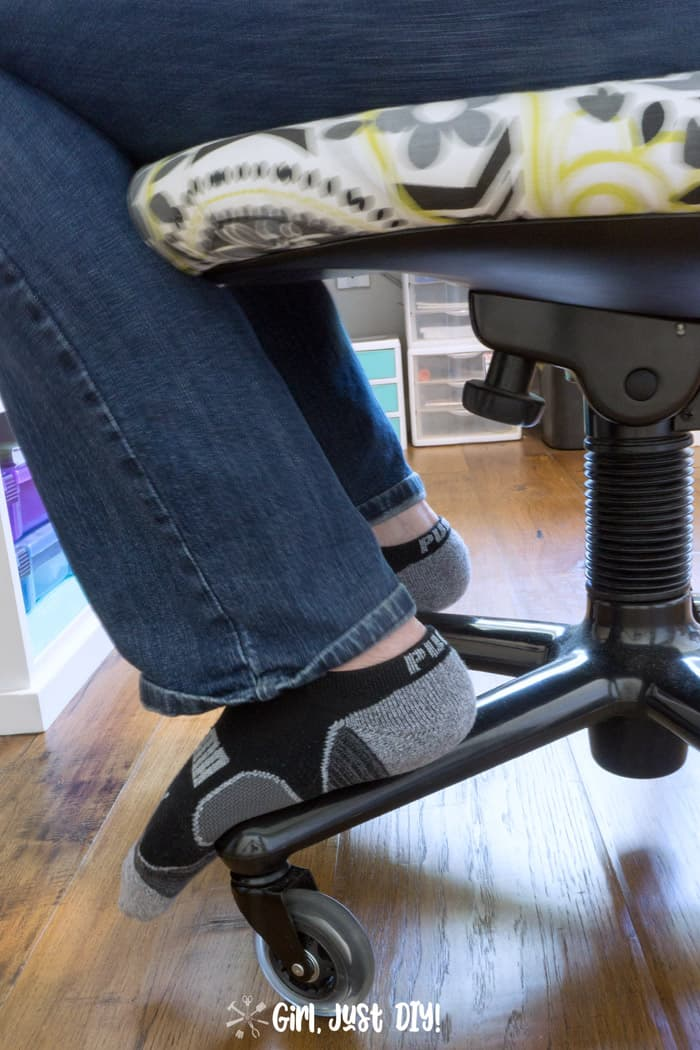 Office chair showing socked feet resting on the chair legs