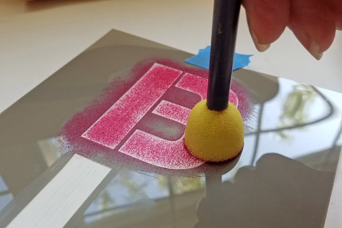 Raspberry Red paint being stenciled onto letter B with foam stippler.