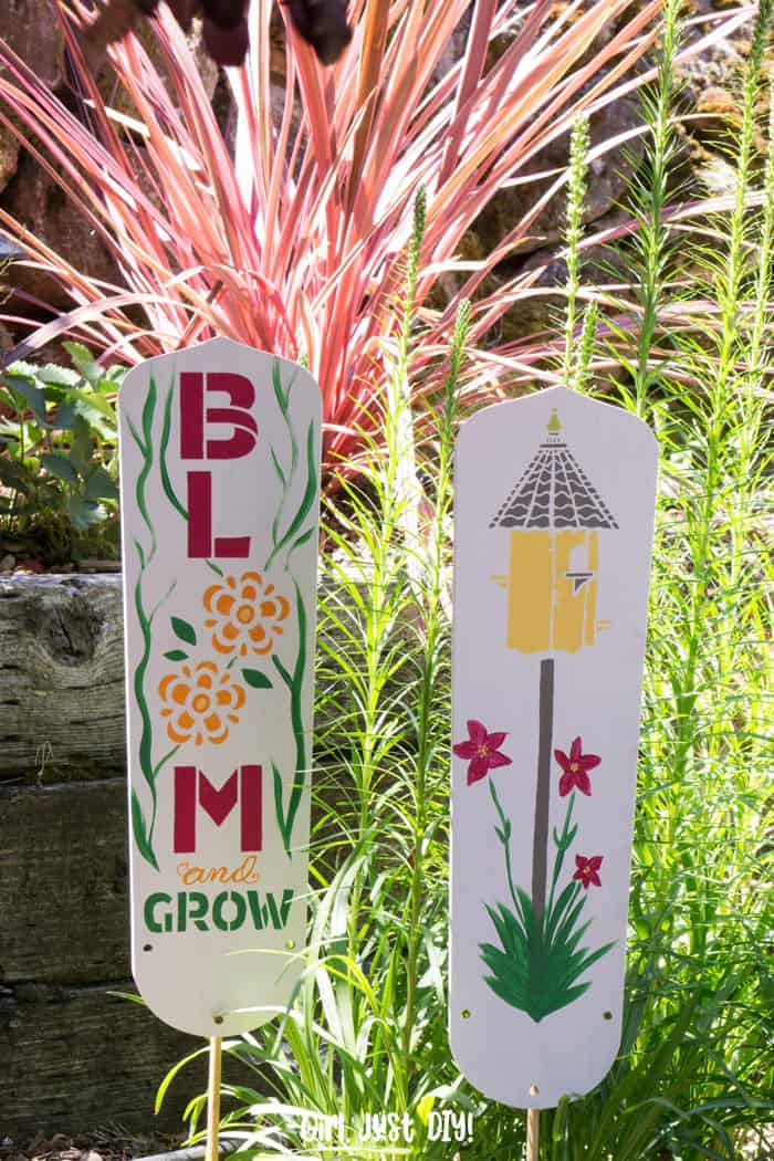DIY Garden Signs from fan blades in front of tall greenery in garden.