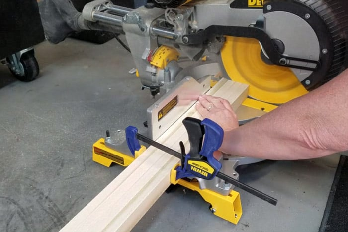 Four boards clamped together getting trimmed at miter saw.