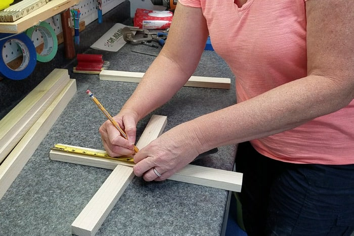 Drawing center hash marks on wood using a ruler and pencil.