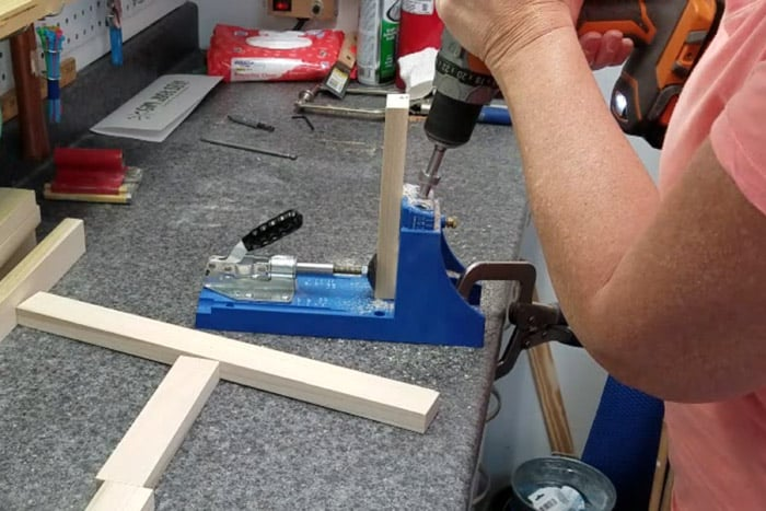Drilling pocket holes into 1x2 board using a Kreg Jig.