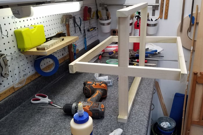 Table base laying on work bench with top and bottom braces connected to the legs.
