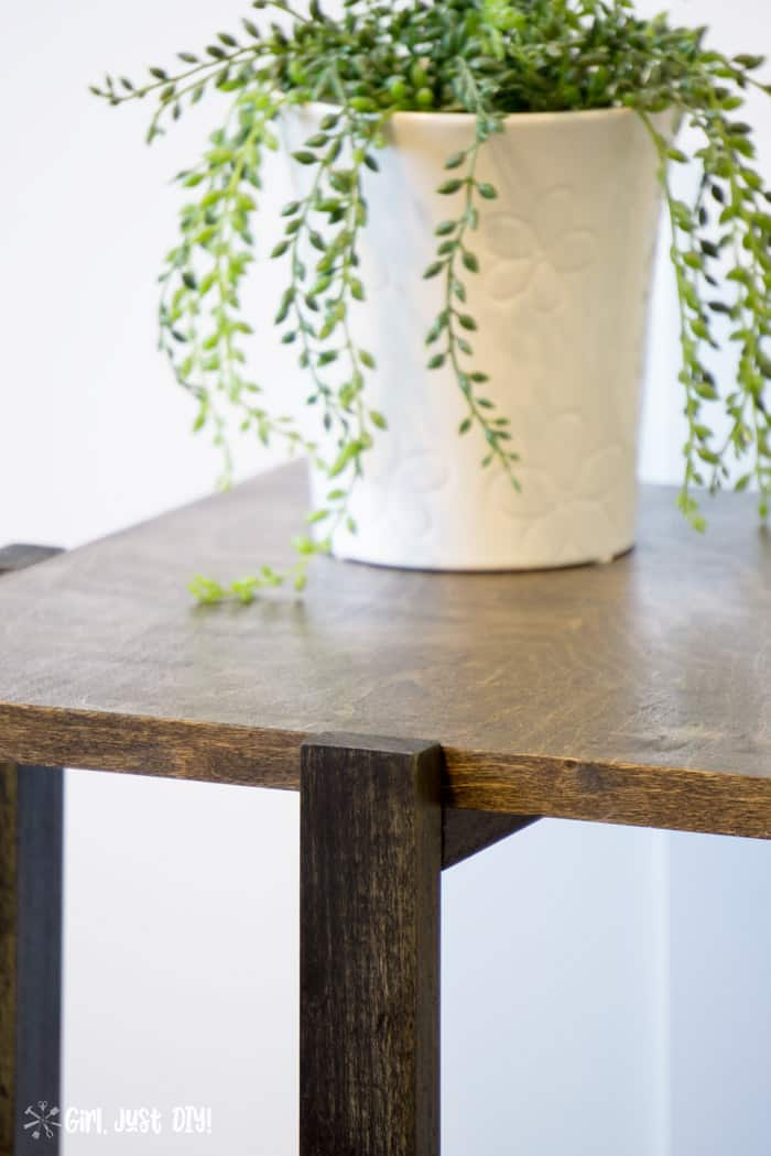Closeup of DIY modern end table showing walnut top contrasting with ebony base.