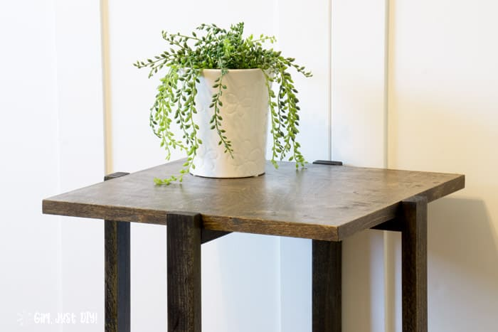 Wide picture of end table topped with houseplant in white pot showing wood tone contrasts.