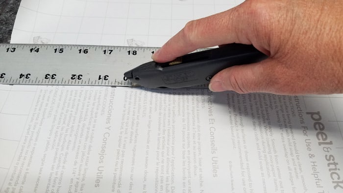 utility knife cutting back of contact paper against metal ruler