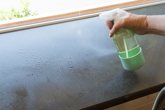 Hand spraying windowsill with bottle of window cleaner.