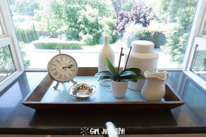 Wooden tray with contact paper bottom in window with ironstone and a clock.