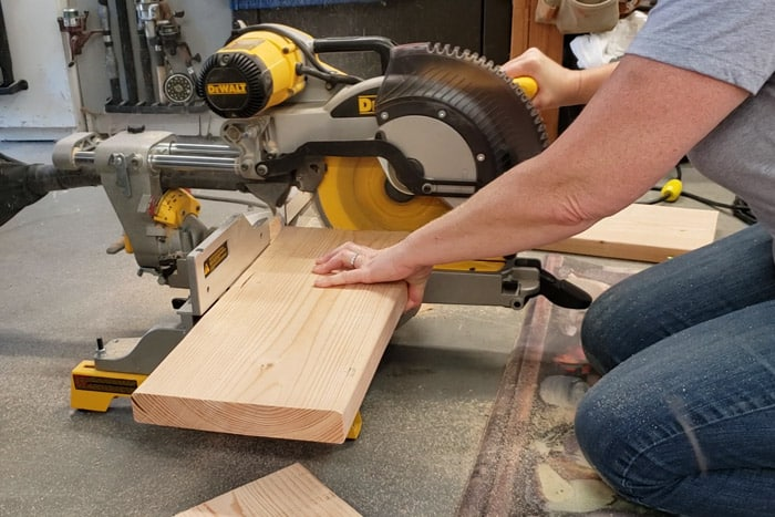 Cutting the 2x10 board on the miter saw to size for the shelves.