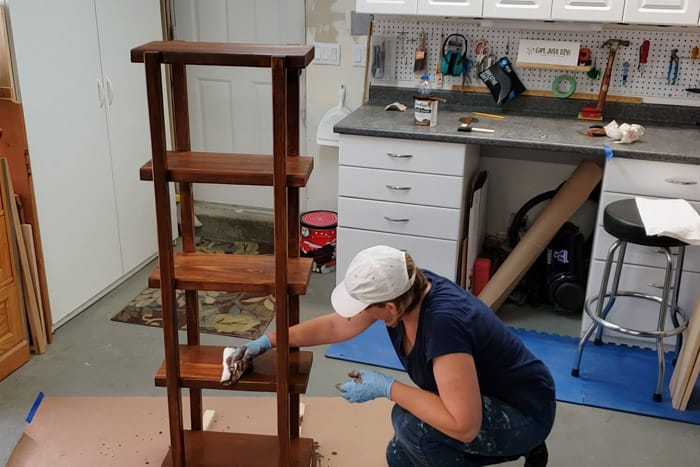 Staining the DIY 2x4 Plant Stand with brown stain.