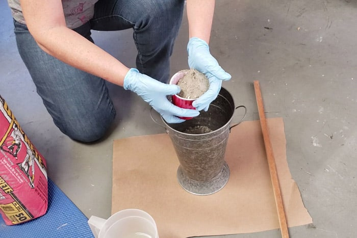 gloved hands adding mortar mix to galvanized bucket.