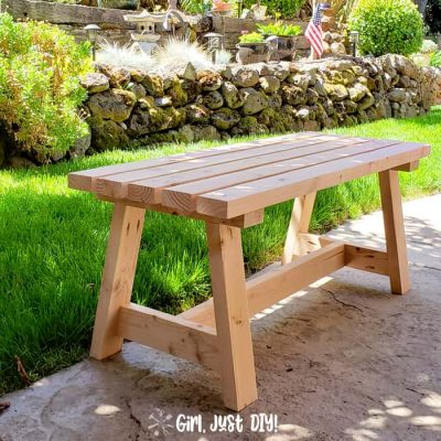Square picture of modern 2x4 bench on patio near lawn.
