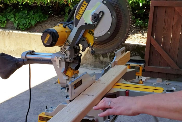 2x4 board on miter saw and being cut for giant jenga game