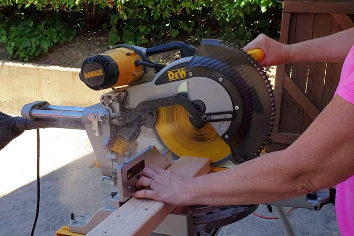 Dewalt brand Miter saw cutting through 2x4 board held by lady's hand.