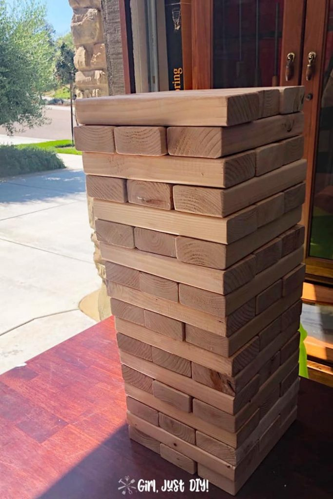 All pieces of diy giant jenga game are stacked on a table ready for play.
