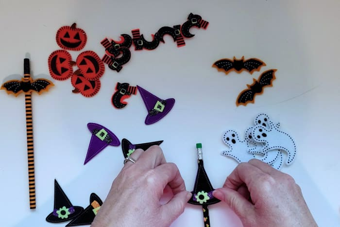 Placing felt witches hat sticker onto pencil.