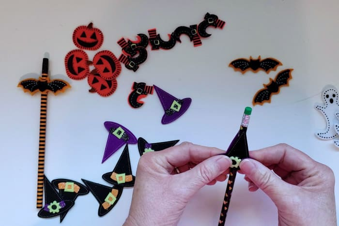 Pressing two felt stickers together that surrounds pencil for the non-candy halloween treats