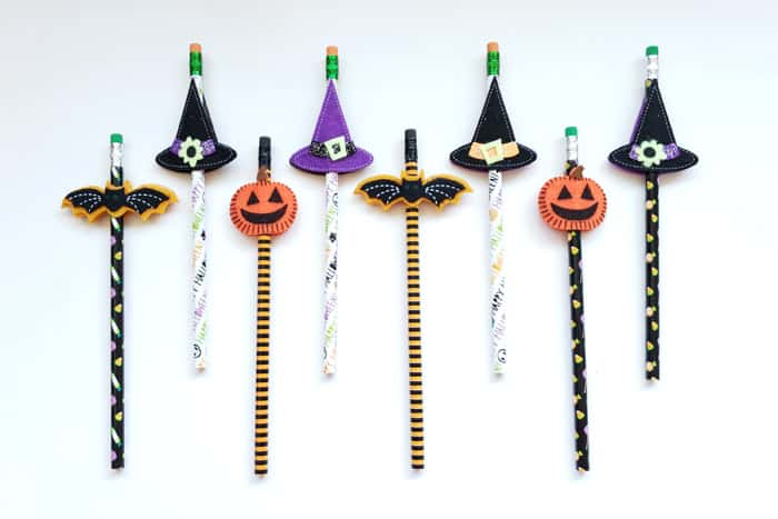 Eight Halloween pencils lined up on table top, bats, hats, and pumpkins.