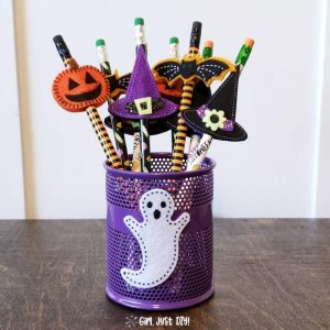Pencil cup filled with non-candy Halloween treats for kids showing pumpkin, bat and witches hat.