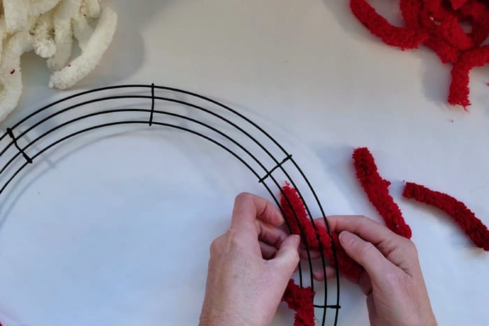 Tying red yarn around the wire of a wreath form.