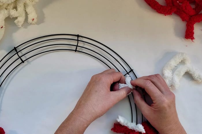 Tying a white piece of fluffy yarn around a wreath form wire.
