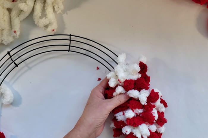 Hand holding wreath form with red and white rows of fluffy yarn.