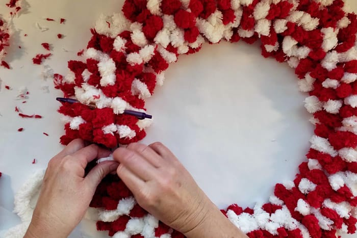 tying the last few rows of red and white fluffy yarn to the wreath form.