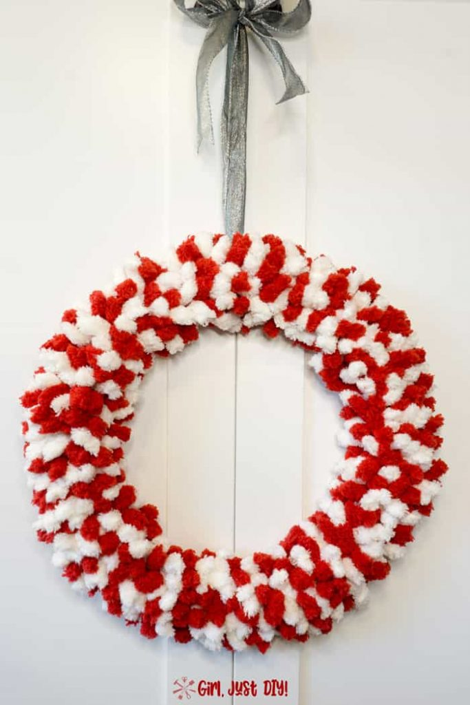 Red and white fluffy christmas wreath with silver ribbon hanger..