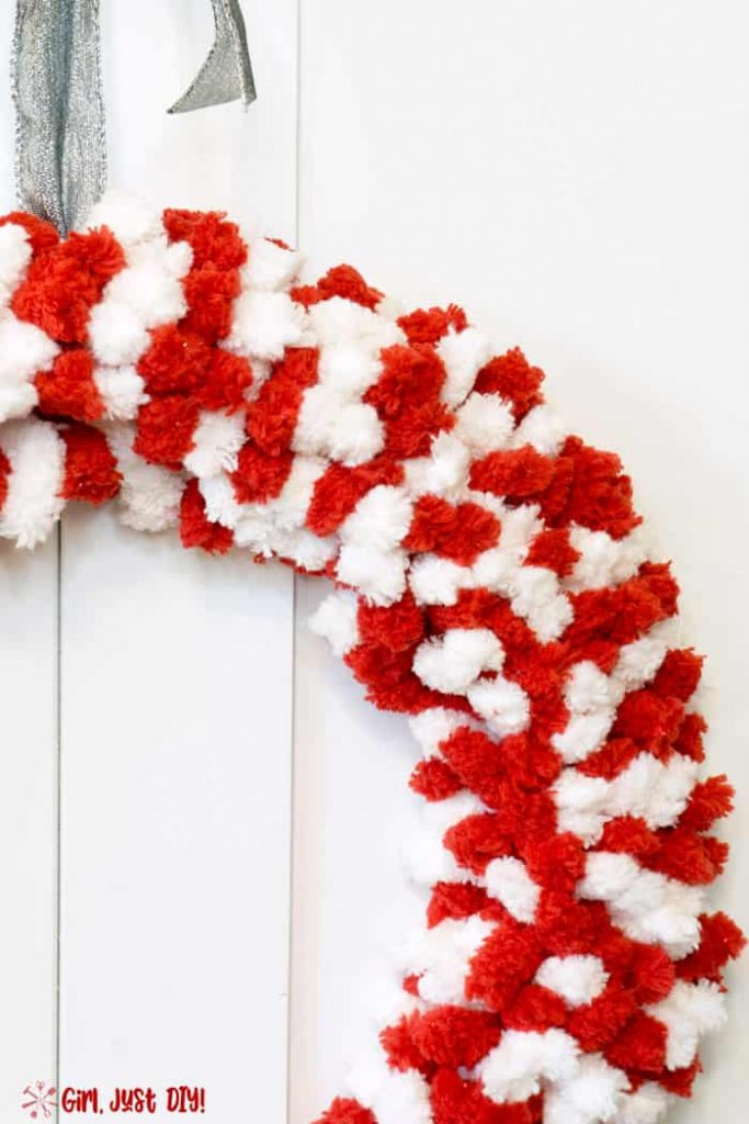 Side picture of Red and white fluffy wreath with silver ribbon on top.