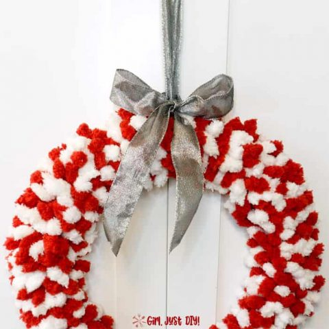 Red and white fluffy christmas wreath with silver ribbon on top.