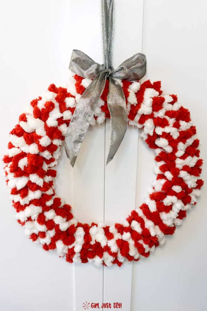 Red and white fluffy christmas wreath with silver bow hanging against a white door.