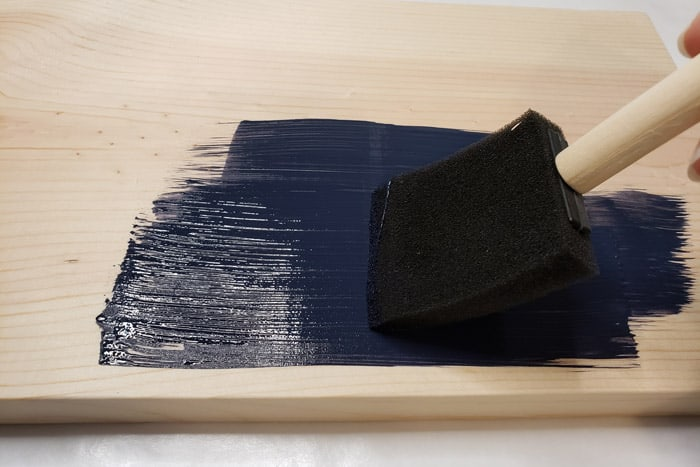 Dark blue paint applied to pine board with foam paint brush.