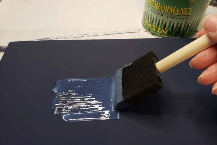 Applying clear coat to blue painted board with foam brush.