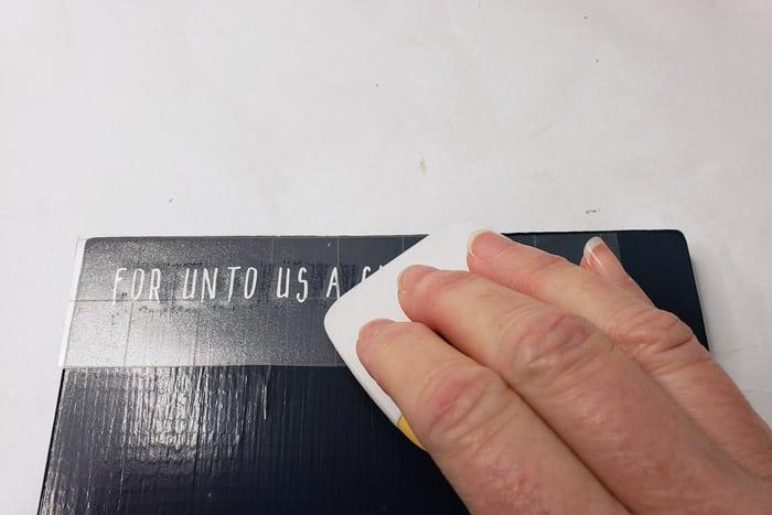 Pressing down on transfer tape with cricut scraper.