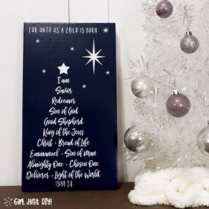 Square image of Christmas Tree Word Art Sign next to white Christmas tree with silver bulbs.